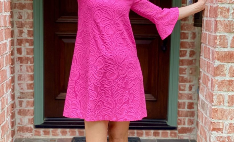 woman wearing neon pink dress standing on front porch