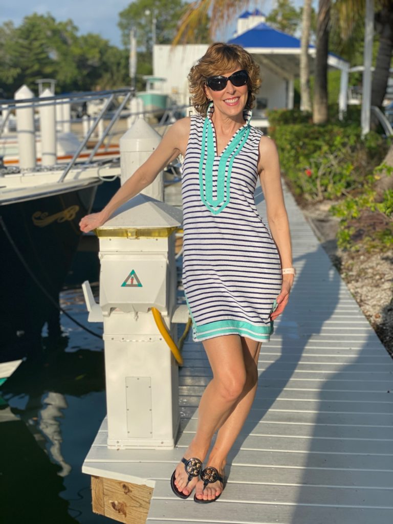 woman in blue and white striped tunic standing on a dock