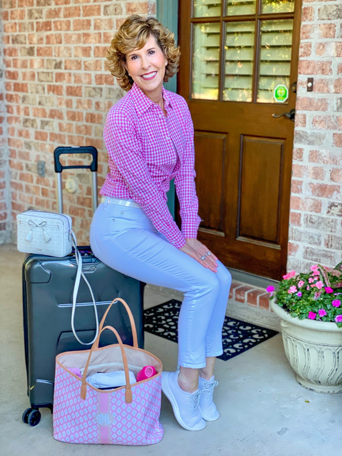 woman in pink gingham shirt sitting on a suitcase