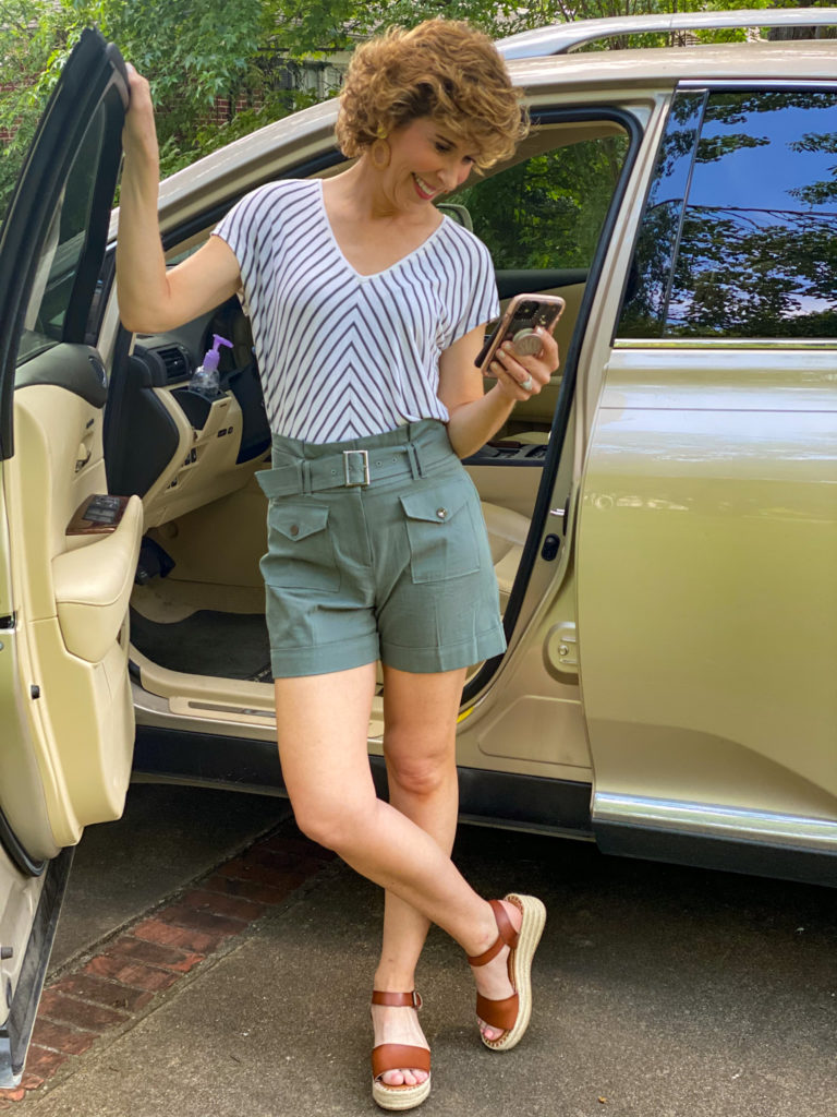 woman in green striped shirt and green shorts standing by car looking at cell phone