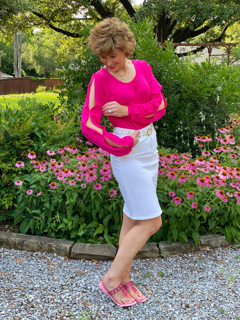 woman in hot pink top and white skirt posing in front of pink flowers