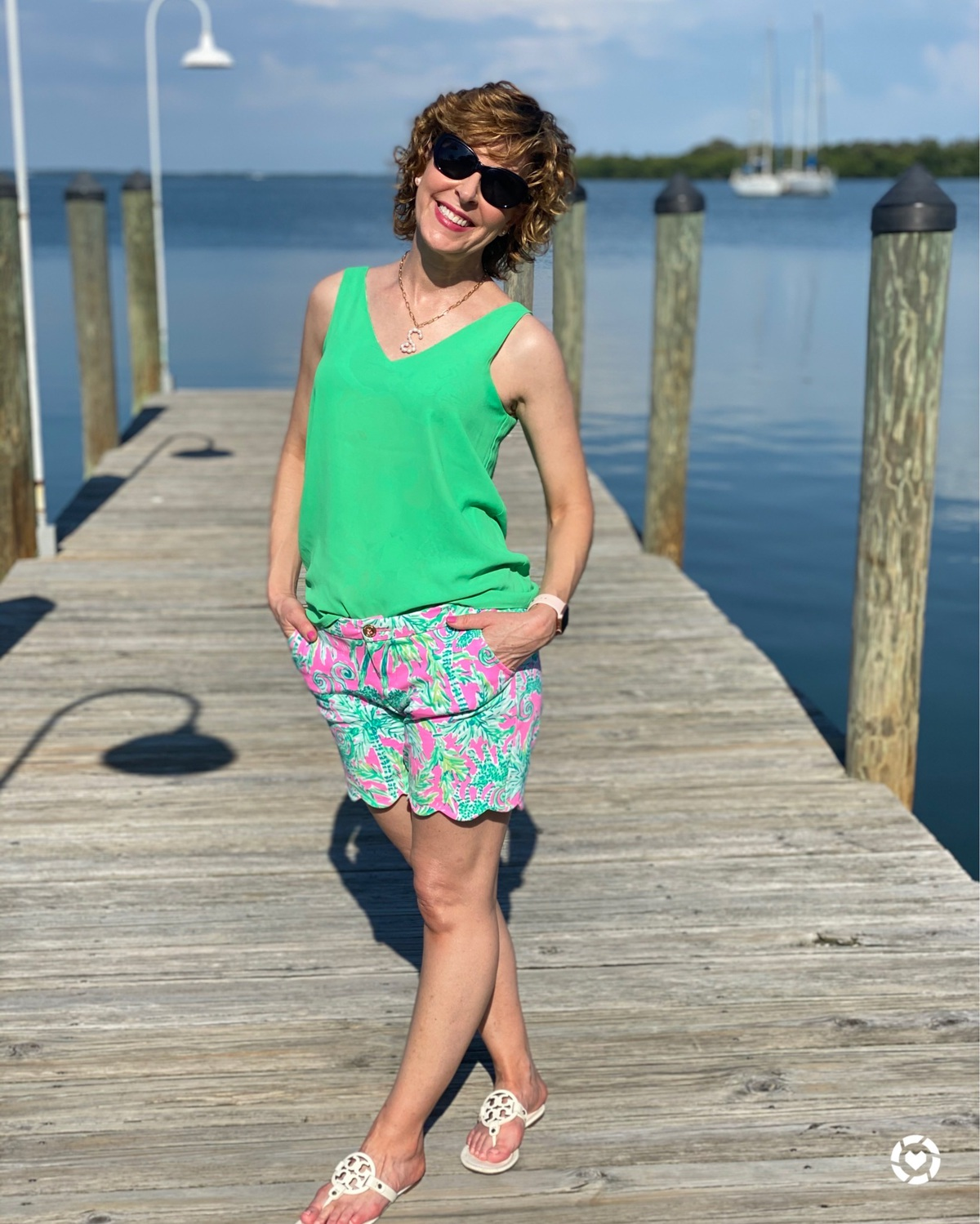 woman wearing green tank top and lilly pulitzer shorts standing on a dock