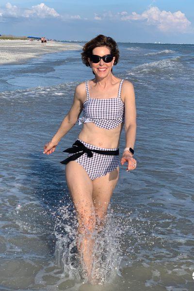 woman in bikini walking through surf
