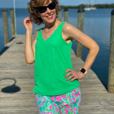 woman wearing green tank top and lilly pulitzer shorts and sunglasses standing on a dock
