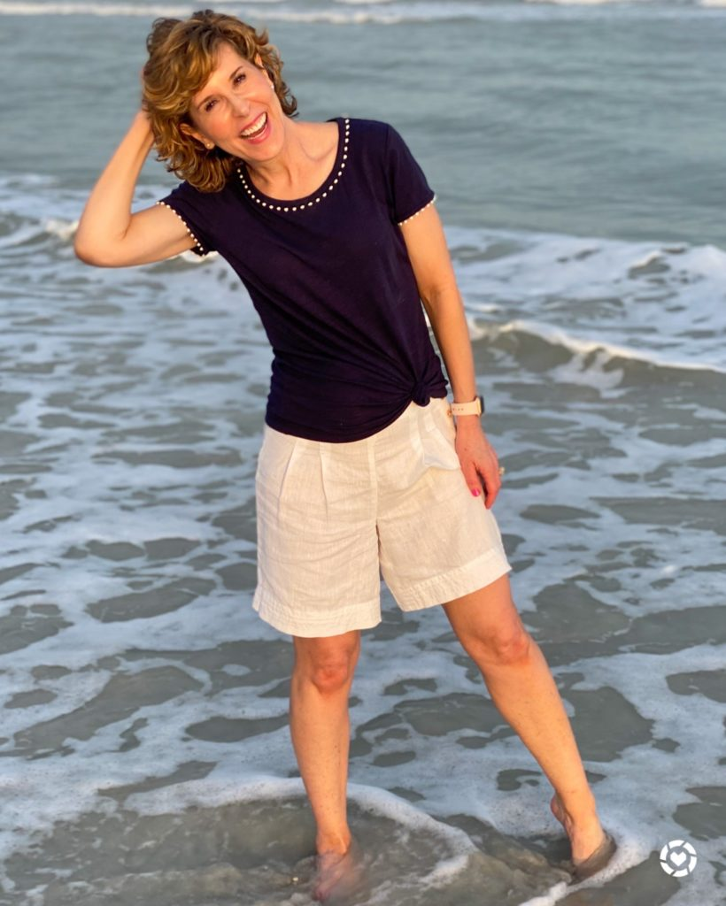 woman in navy tee and white linen shorts standing in the shallow water at the beach