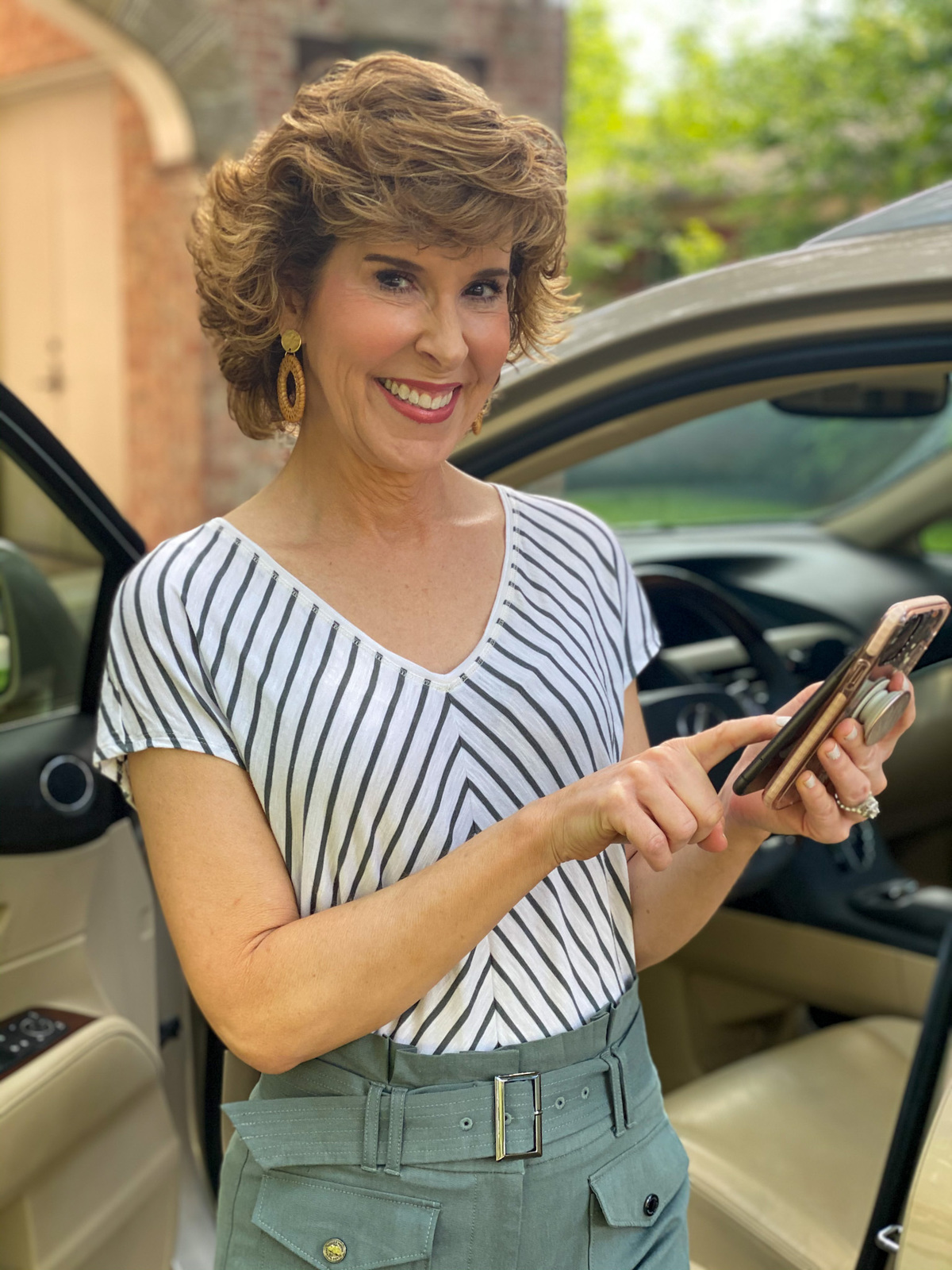 woman in green striped shirt standing by car looking at cell phone