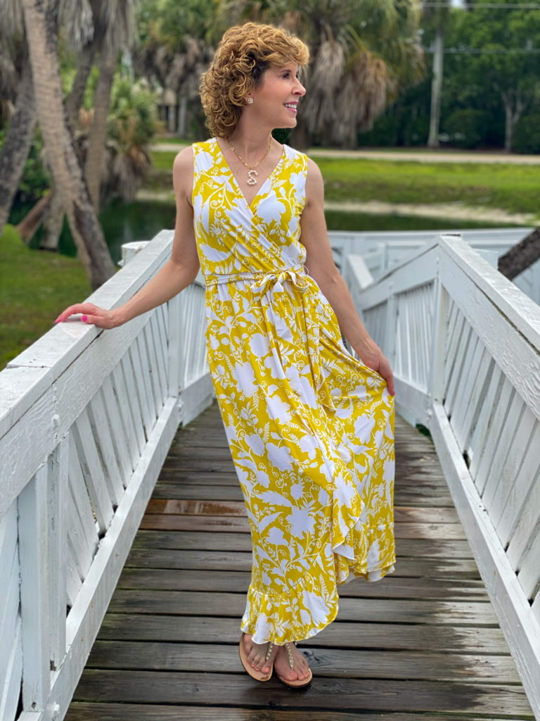 woman in yellow maxi dress standing on a white bridge
