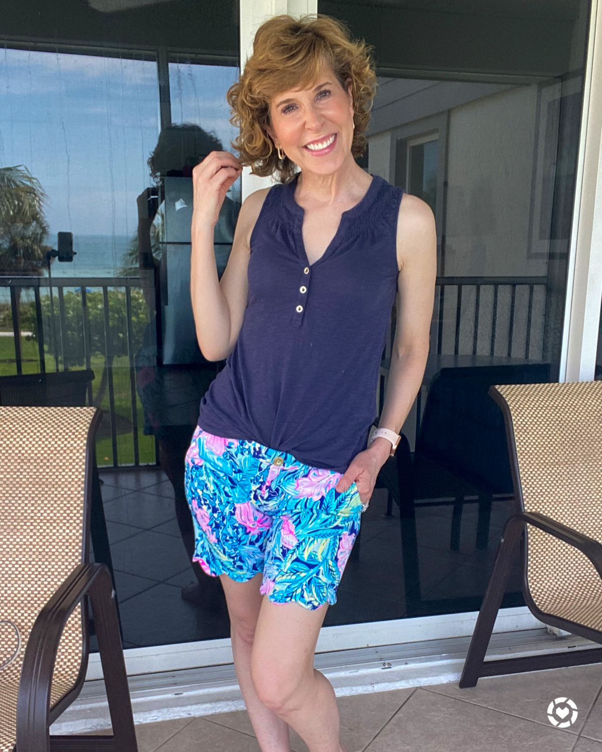 woman wearing lilly pulitzer short and top standing on patio