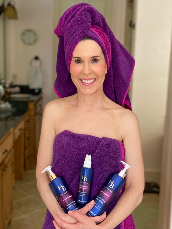 woman with hair over 50 dressed in a purple towel and holding hair biology volumizing treatement and a pink blow dryer