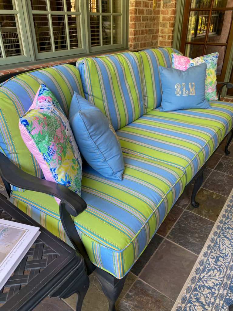 outdoor sofa with blue and green striped fabric cushions