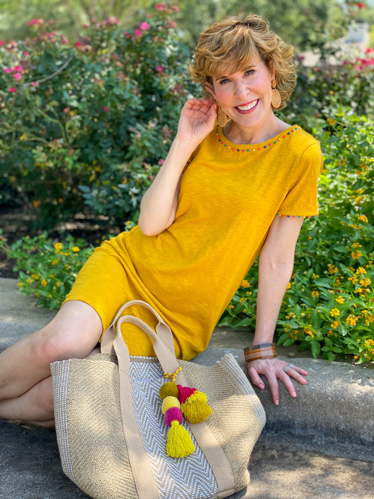 woman wearing boden gold charlie jersey dress sitting on curb by chico's jute tote