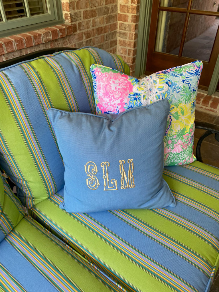 frontgate blue monogrammed square pillow sitting on striped cushion patio furniture