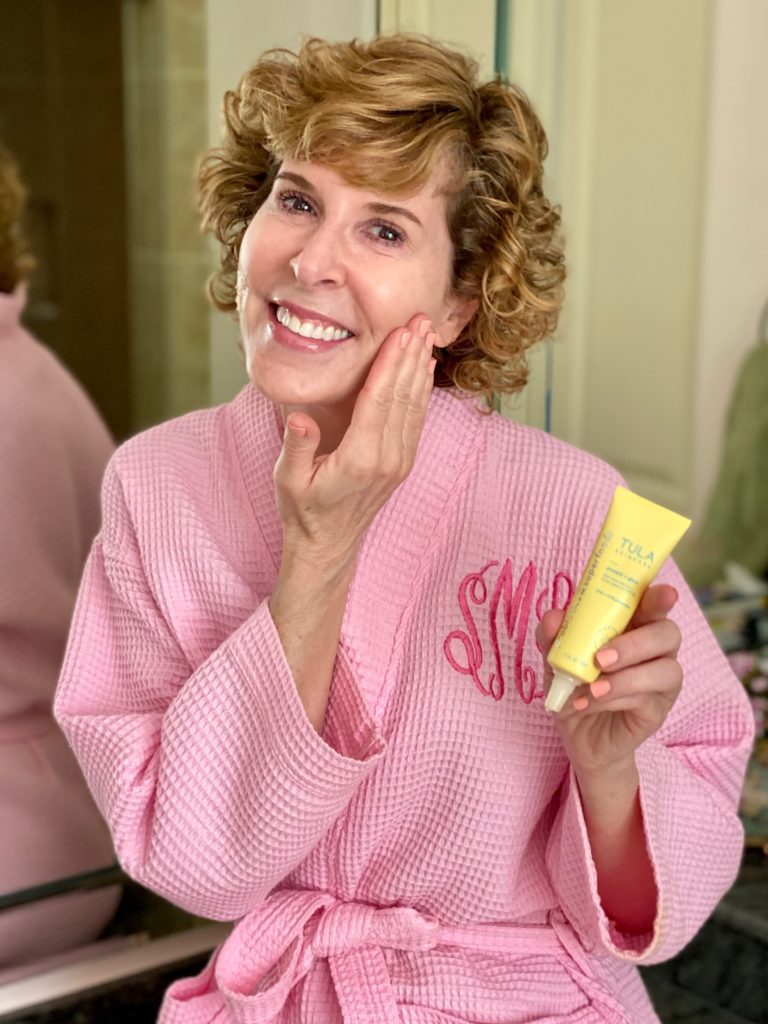 woman dressed in pink robe rubbing tula protect and glow sunscreen on her cheek
