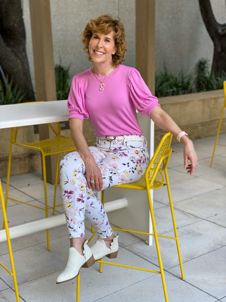 woman looking into camera in pink top and floral jeans sitting on a yellow chair on a patio thinking weekend thoughts