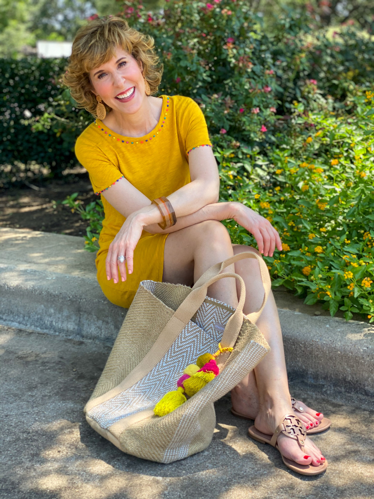 woman in gold boden charlie jersey dress sitting on a curb with a jute bag