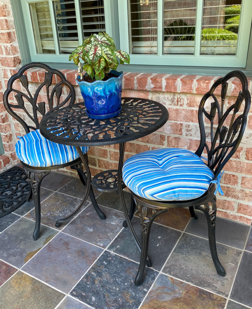 bistro table and chair set with blue striped cushions on back patio