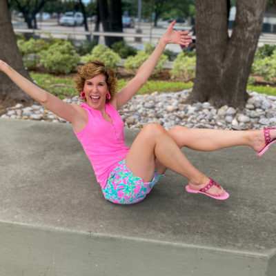 woman in neon pink top and floral shorts looking excited