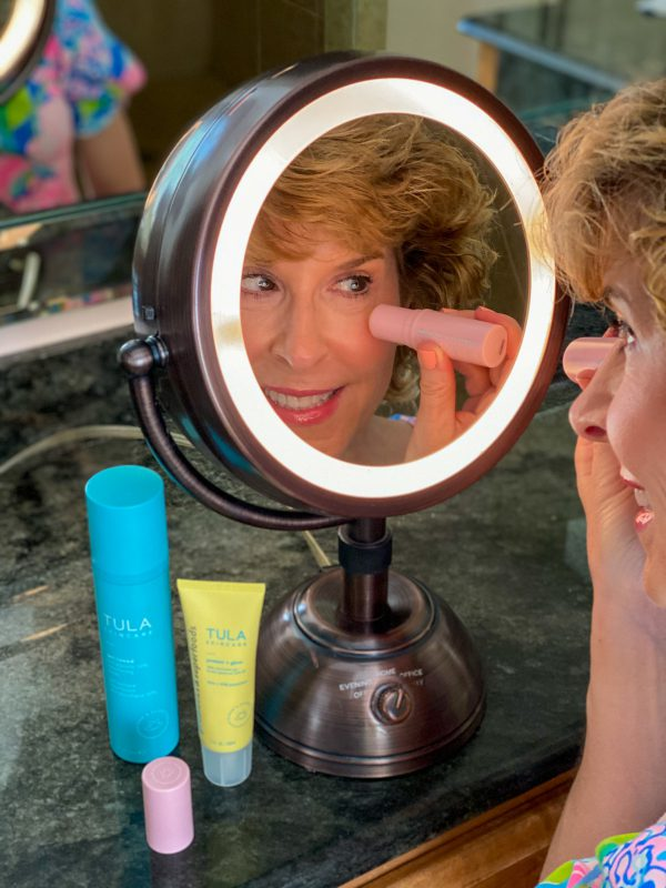 woman applying clean beauty product from pink tube to undereye area
