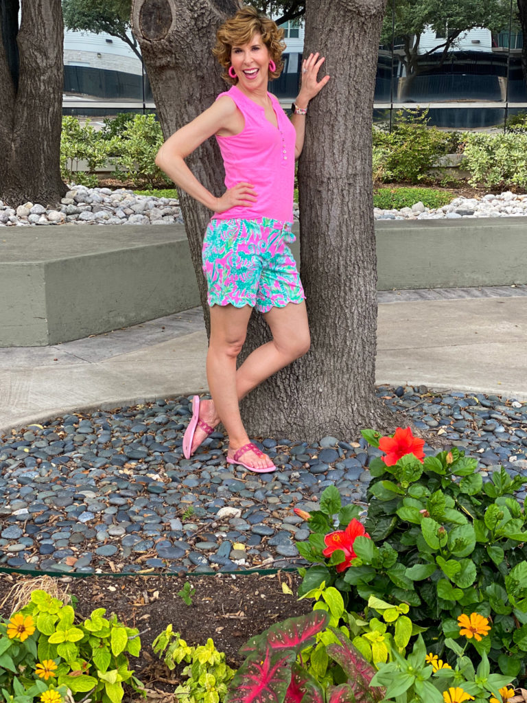 woman in neon pink top and floral shorts posing by a tree
