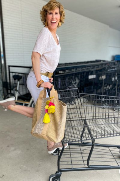 woman wearing tan tee and white shorts playfully standing on back of grocery cart doing weekend shopping