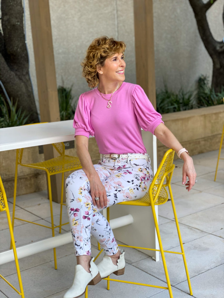 woman in pink top and floral jeans sitting on a yellow chair on a patio thinking weekend thoughts