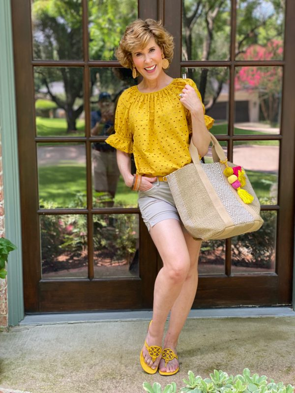 woman dressed in yellow eyelet top and tan shorts carrying burlap tote with tassels standing on porch in front of french doors