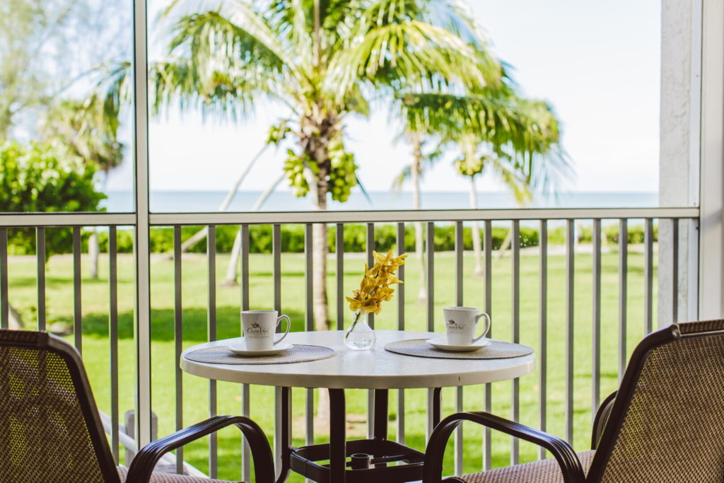 lanai of beach condo looking out at table and chairs and palm tree and beach