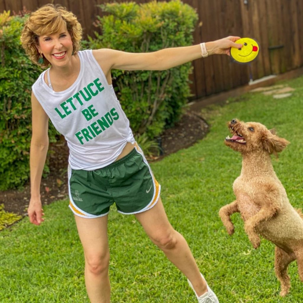 woman wearing lettuce be friends tank top and playing with dog