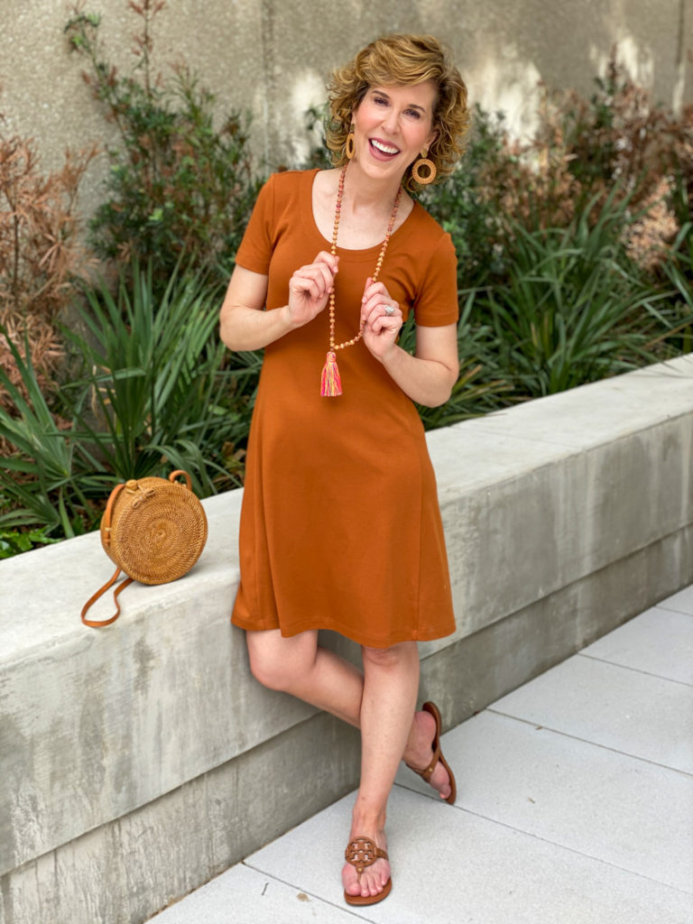 woman in light brown dress standing and holding her tassel necklace on the weekend