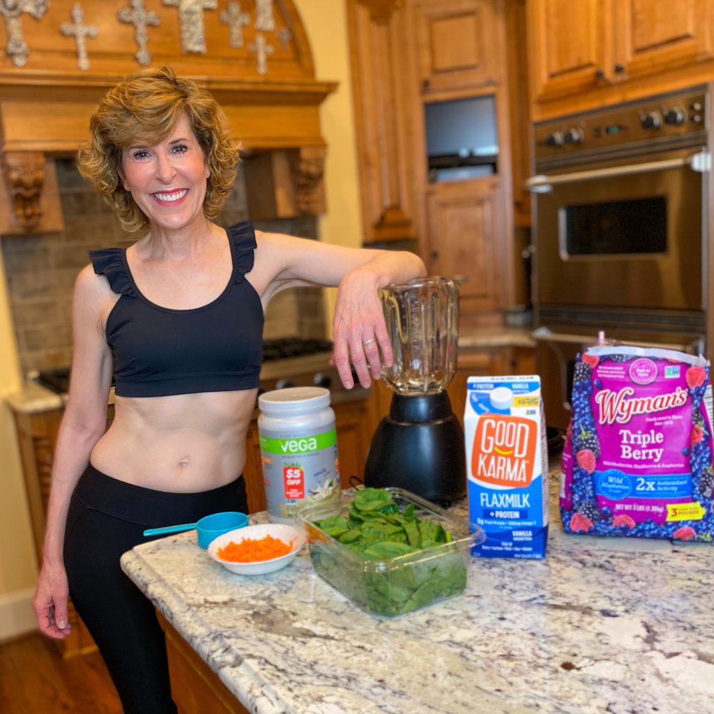 woman wearing black ruffle strap sports bra and black crop leggings standing by ingredients to make a smoothie