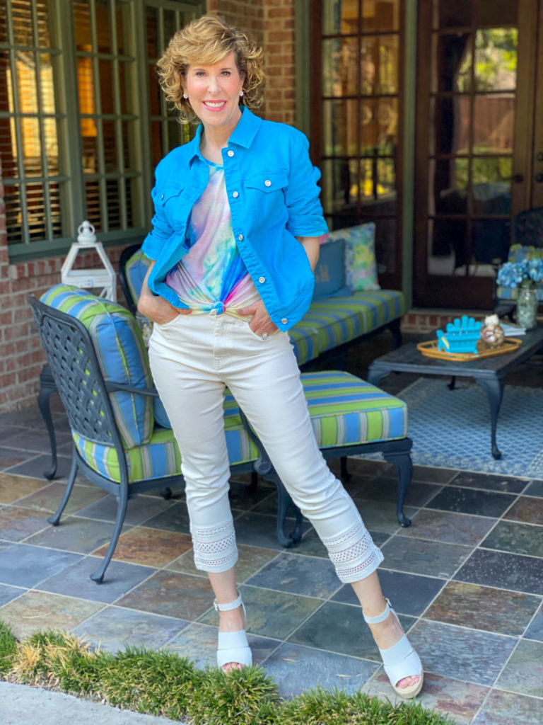 woman wearing white diane gilman jeans and tie dye tee with bright turquoise blue jeans jacket standing on porch