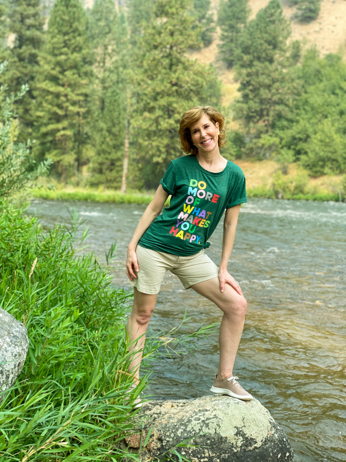 woman wearing graphic tee standing by a river