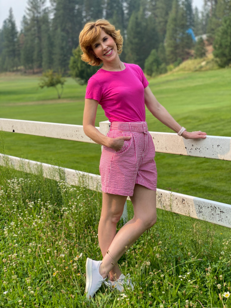 woman wearing pink tee and striped shorts standing by a white fence