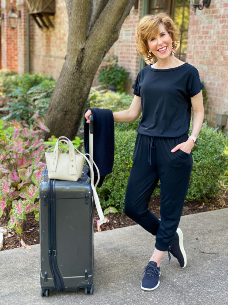 woman in black jumpsuit standing by a suitcase getting ready to leave town for the weekend