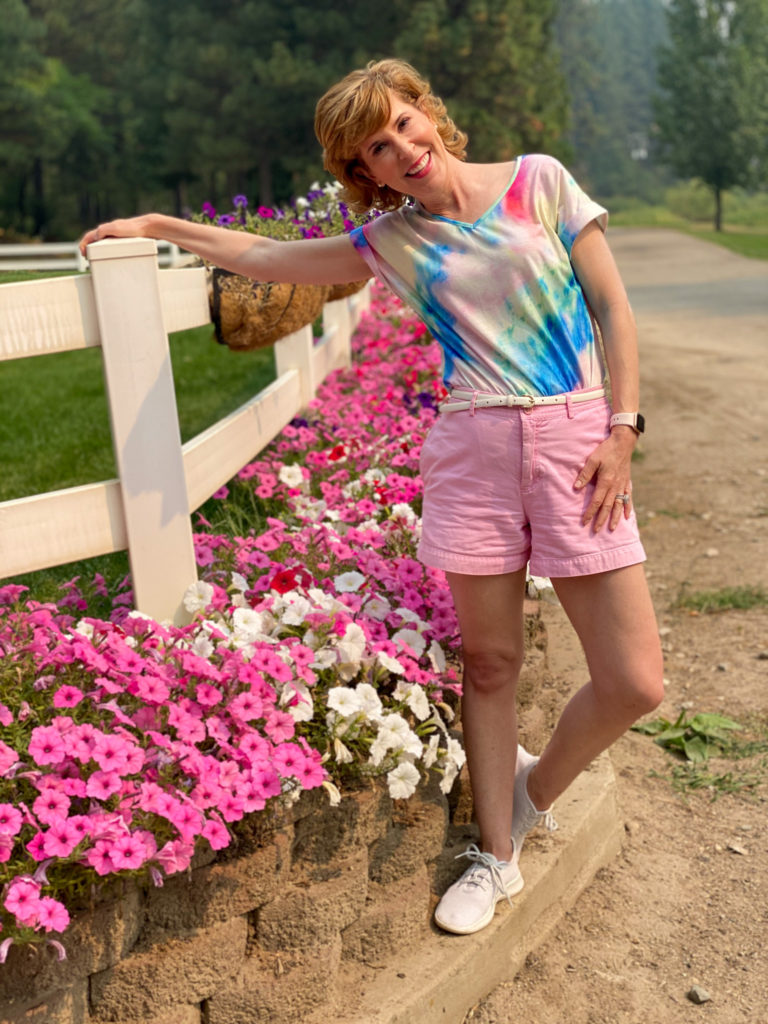 woman wearing tie dye shirt and pink shorts standing by white fence and flowers