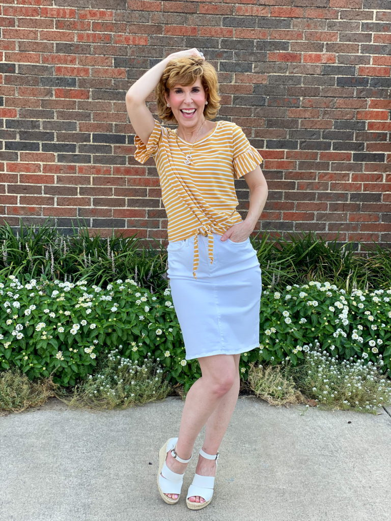 woman over 50 wearing yellow tee and nydj five pocket white skirt