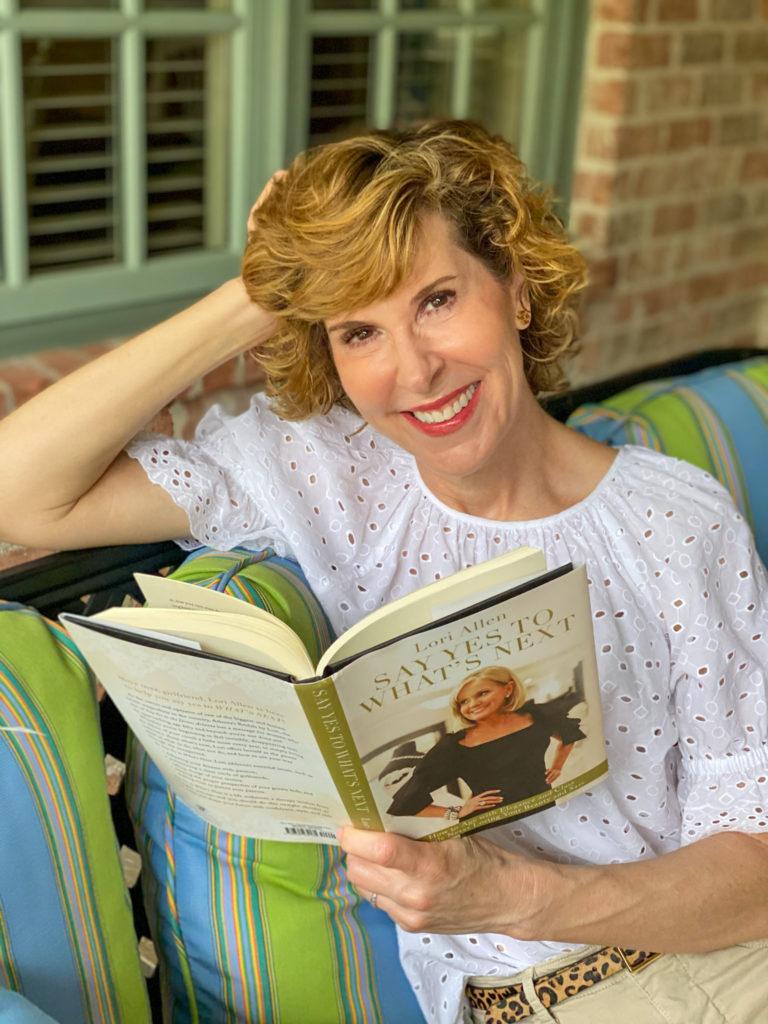 woman wearing eyelet top reading book