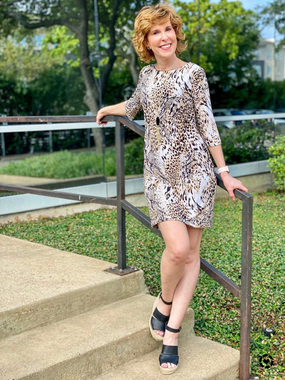 woman in animal print dress leaning against a stair railing in front of an office building