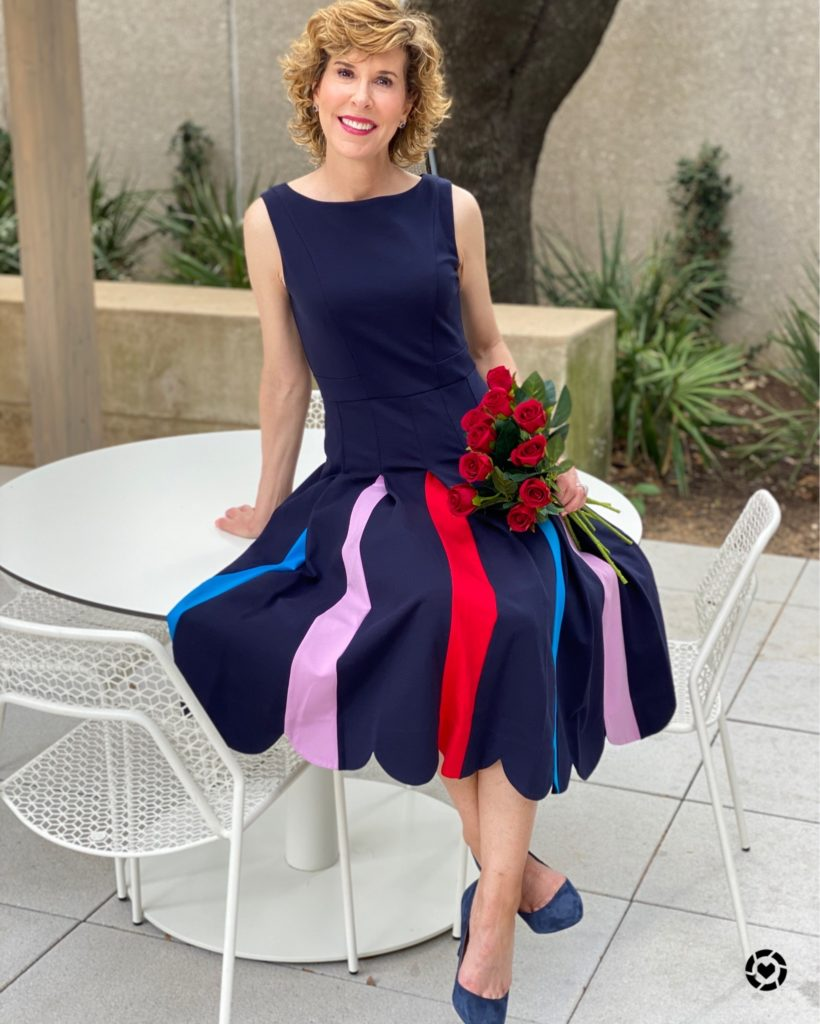 woman wearing navy blue dress with multi-colored skirt sitting on a white table