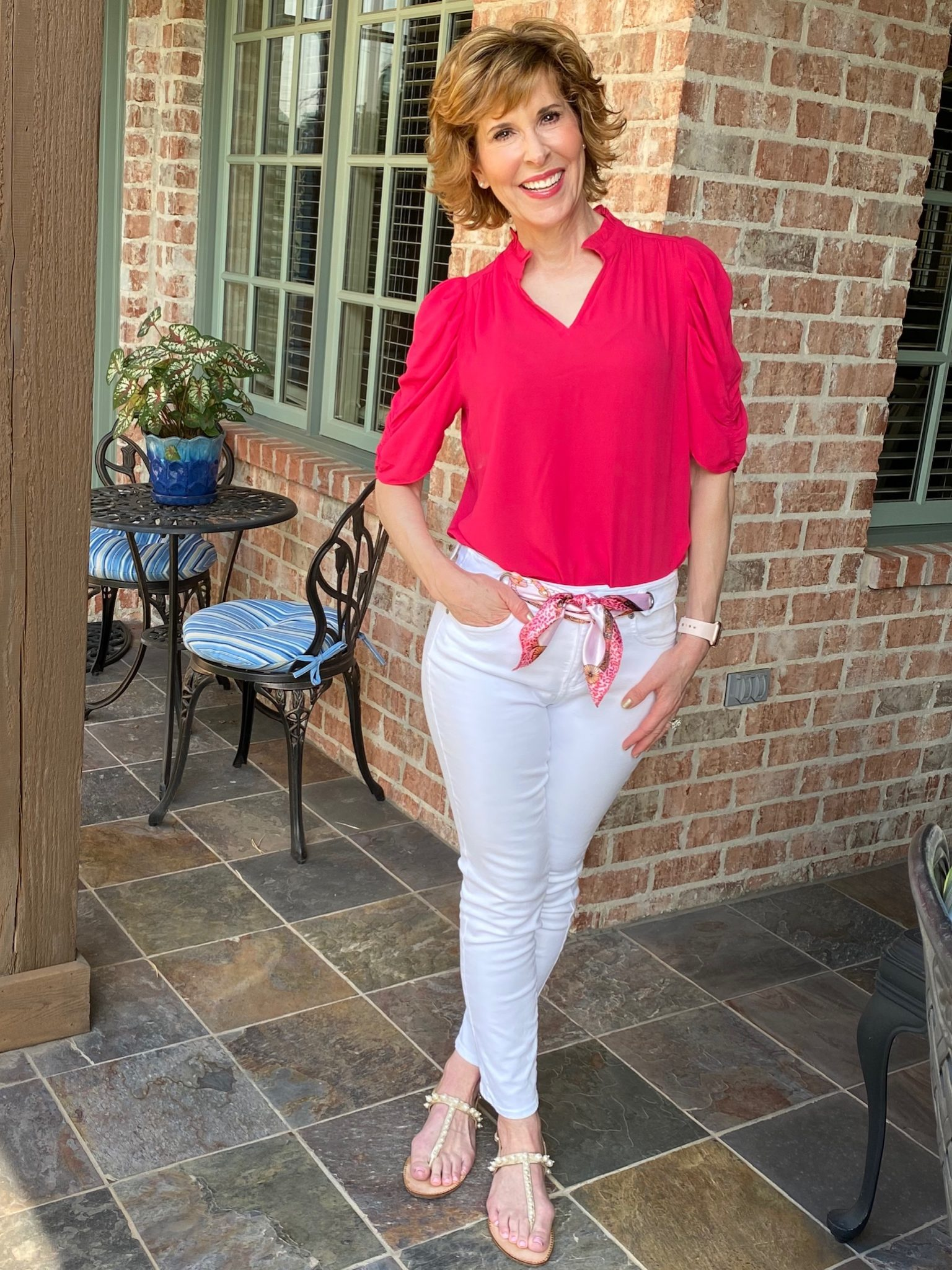 woman wearing lark & ro ruffle neck georgette top and nydj white scarf-tie alina jean standing on porch