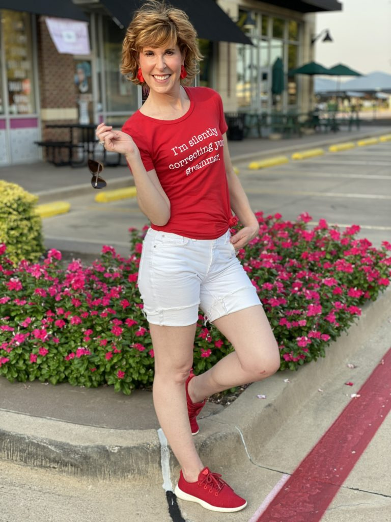 woman standing in parking lot wearing graphic red tee
