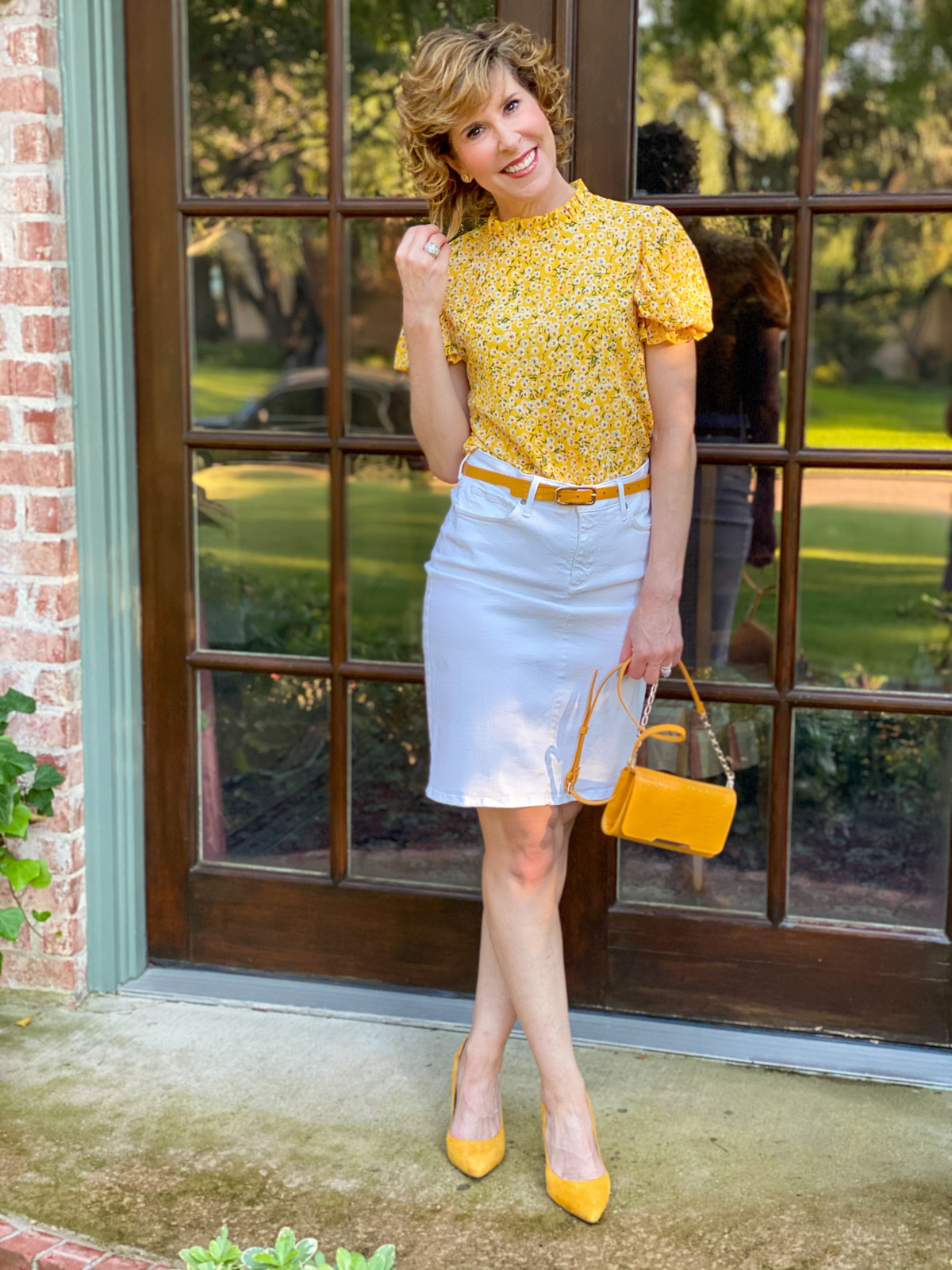 woman wearing yellow ruffle neck top and white skirt standing in front of doors