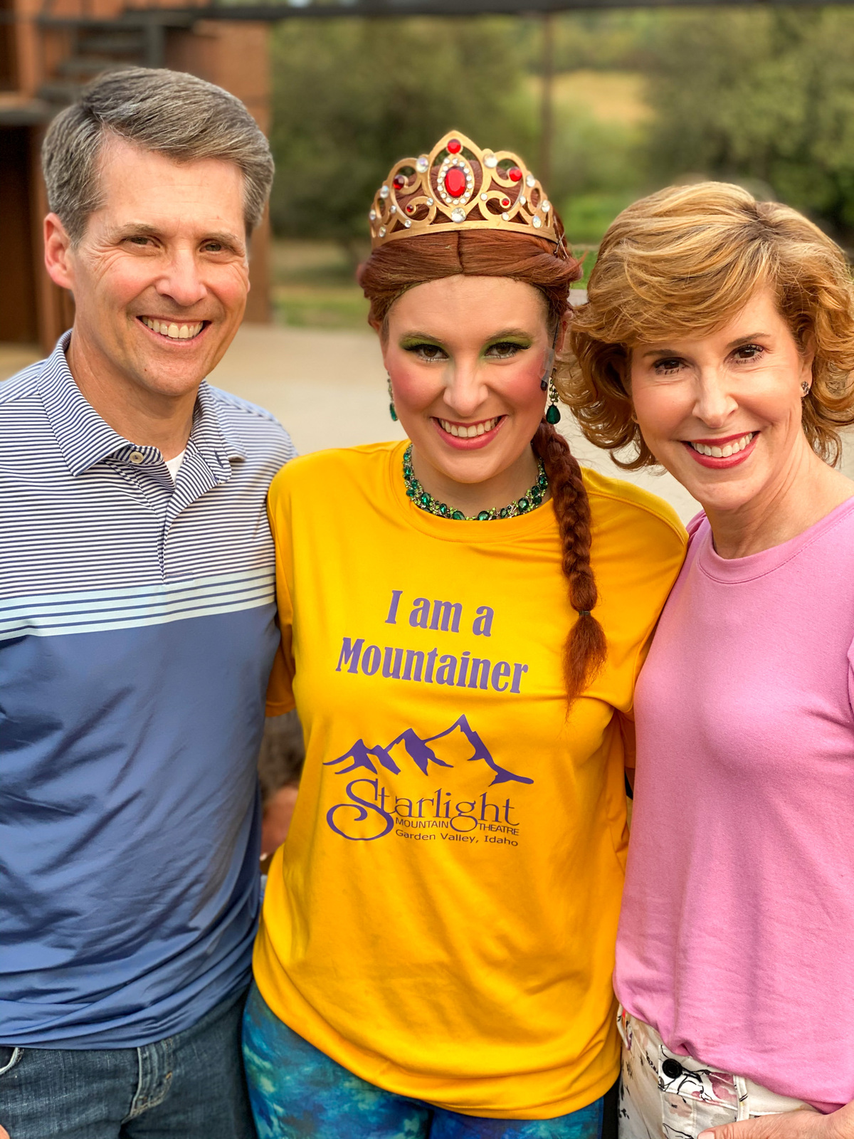 woman and man standing on either side of girl in yellow tee in a princess tiara