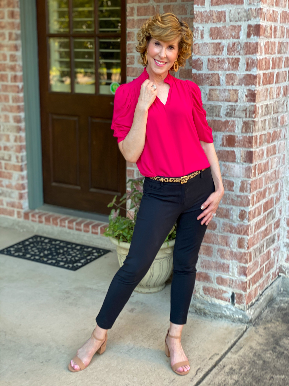 woman wearing ruffle neck georgette top and black ankle pants standing by brick wall