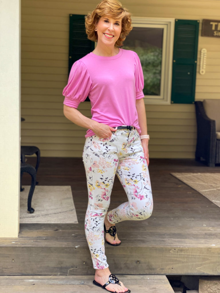 woman wearing pink puffy sleeve tee and floral pants standing on a porch step