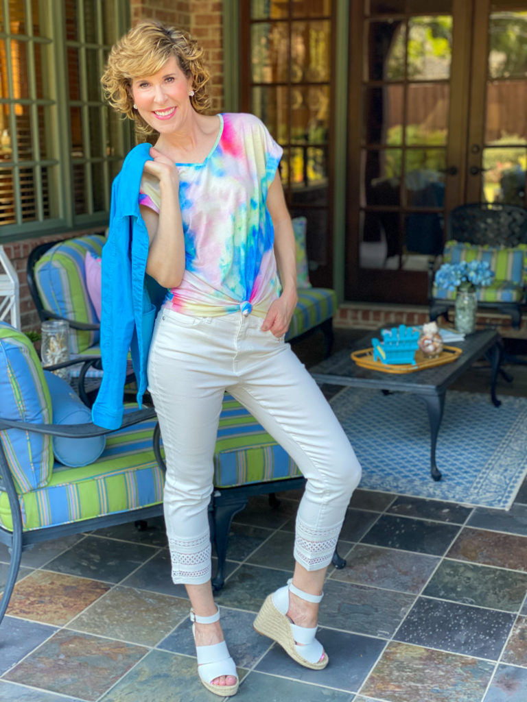 woman wearing white diane gilman jeans and tie dye tee standing on porch