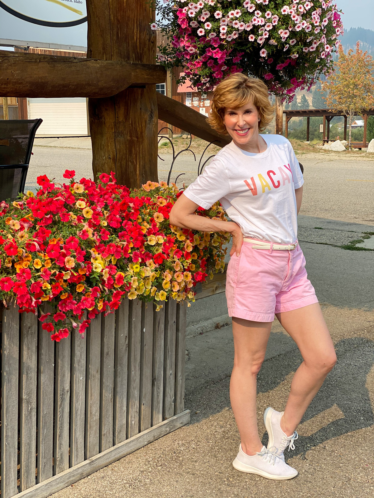woman wearing vacay tee and pink shorts standing by flowers