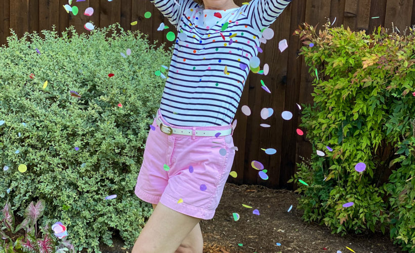 woman wearing pink shorts and striped top throwing confetti in the air