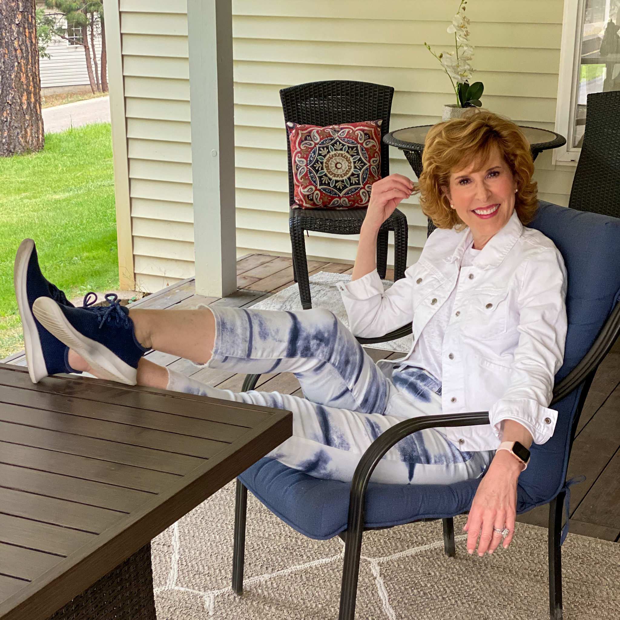 woman wearing tie dye jeans and white jeans jacket sitting with her feet up on a table on a porch