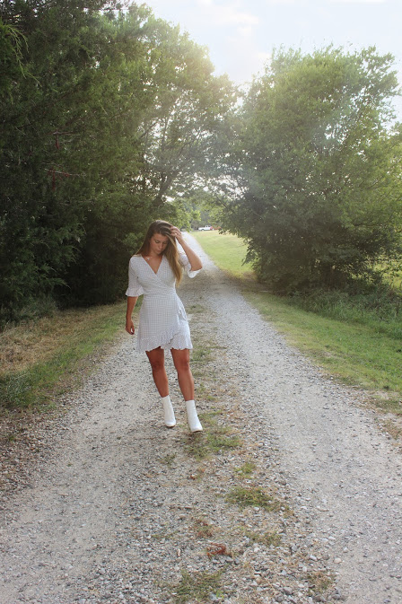 girl in white dress and white booties walking on a dirt road with the sun behind her